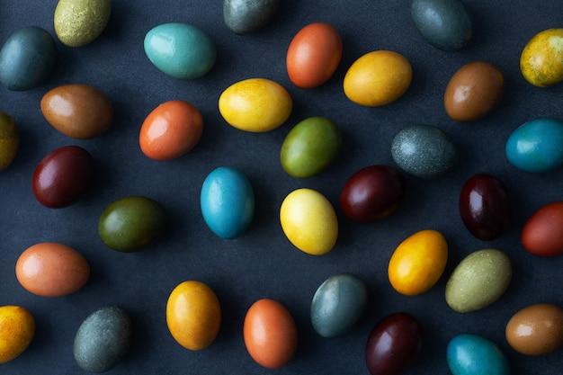 Dunkler osterhintergrund mit eiern, die mit natürlichem farbstoff gefärbt sind - zwiebelschale, kurkuma, rotkohl, kaffee, kadaver.