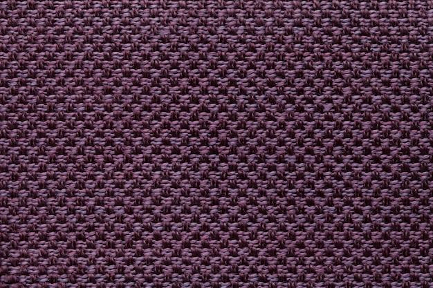 Dunkler purpurroter textilhintergrund mit kariertem muster, nahaufnahme. struktur des gewebemakros.