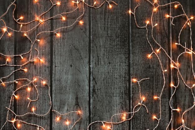 Dunkler rahmen der weihnachtsbeleuchtung auf grauem hölzernem hintergrund