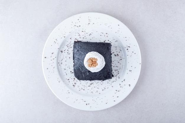 Dunkler schokoladenbrowniekuchen mit walnuss auf teller auf marmortisch.