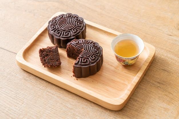 Dunkler schokoladengeschmack des chinesischen mondkuchens auf holzteller