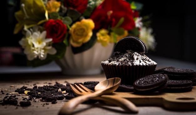 Dunkler schokoladenkleiner kuchen mit schokoladenplätzchen auf dem hölzernen tabellen- und blumenhintergrund. Premium Fotos