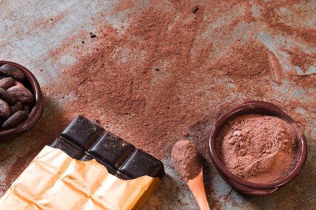 Dunkler schokoriegel mit zerstreutem kakaopulver und bohnen rollen auf rustikalem hintergrund