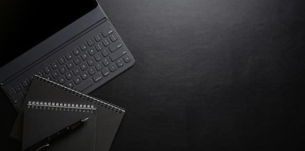 Dunkler stilvoller arbeitsplatz mit laptop-computer und büroartikel auf schwarzem schaumschreibtisch