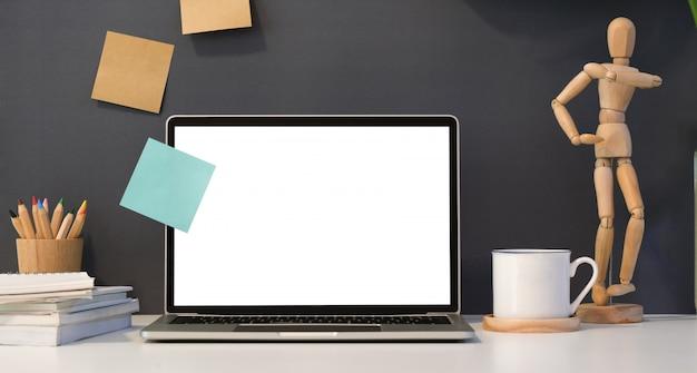 Dunkler stilvoller arbeitsplatz mit offenem laptop des leeren bildschirms