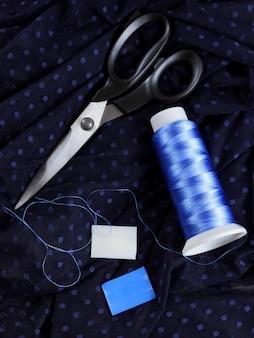 Dunkler stoff mit tupfen und blauem seidenfaden. prozess des schneiderns. schere und fadenspule auf schwarzem stoff.