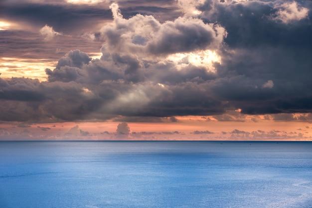 Dunkler sturm bewölkt mit sonnenlicht-streamer im blauen meer am abend