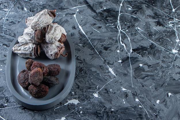 Dunkler teller mit getrockneten leckeren kakis und datteln auf marmorhintergrund.