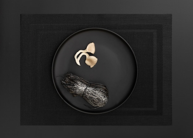 Dunkler teller mit nudeln und champignons auf einem dunklen tuch