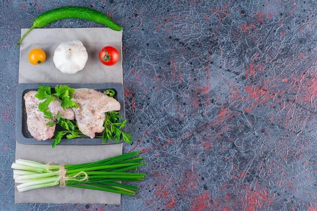 Dunkler teller mit rohen hühnerflügeln auf marmoroberfläche.