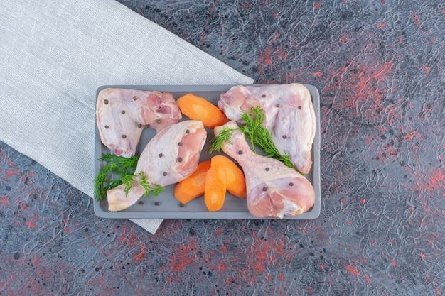 Dunkler teller mit rohen hühnertrommelstöcken auf marmoroberfläche.