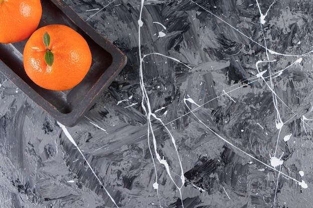 Dunkler teller mit saftigen ganzen und geschnittenen orangen auf marmoroberfläche