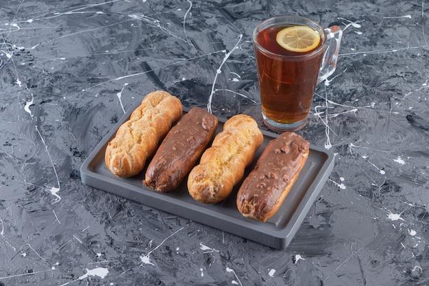 Dunkler teller mit schokoladen-eclairs und glas tee mit zitrone auf marmoroberfläche.