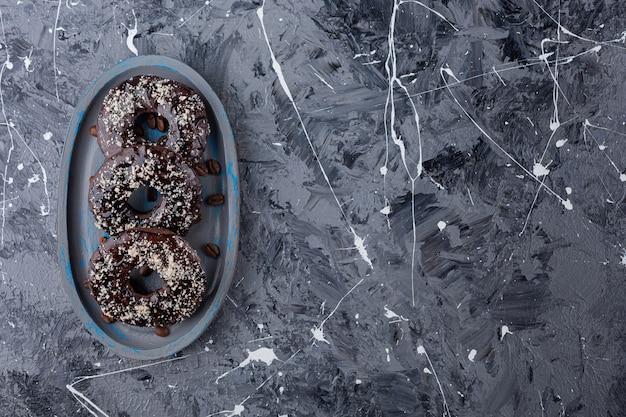 Dunkler teller mit schokoladendonuts mit kokosnussstreuseln auf marmor.