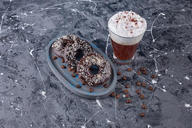 Dunkler teller mit schokoladendonuts mit kokosnussstreuseln und leckerem kaffee auf marmor.