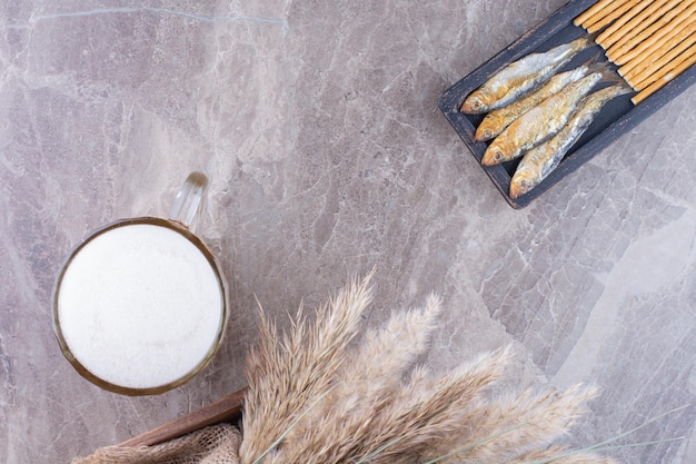 Dunkler teller mit snacks und schaumigem bier auf marmoroberfläche. foto in hoher qualität