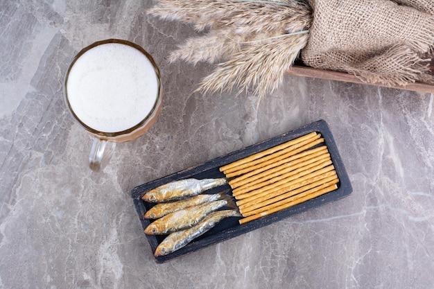 Dunkler teller mit snacks und schaumigem bier auf marmoroberfläche