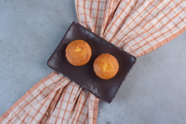 Dunkler teller mit süßen minikuchen auf steinhintergrund.