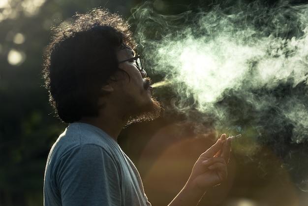 Dunkler und mürrischer schuss eines rauchenden mannes