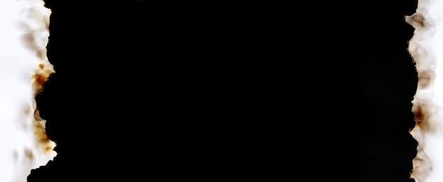 Dunkles banner des verbrannten alten zerrissenen weißen papierrahmens auf schwarzer oberfläche mit kopienraum