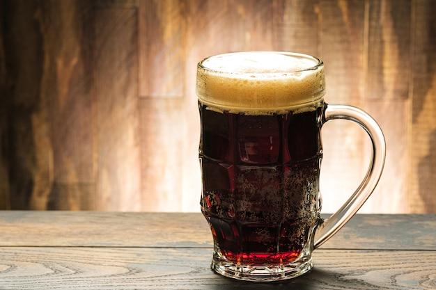 Dunkles bier im glas auf tisch im pub mit kopierraum