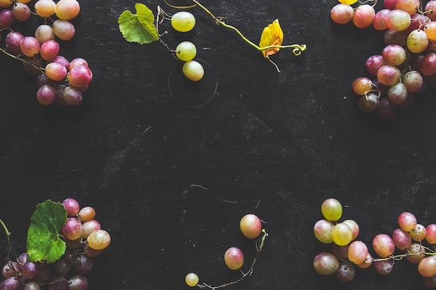 Dunkles essen - frische unpolierte dunkelrote schwarze trauben auf schwarzem schiefersteinhintergrund mit kopierraum oben