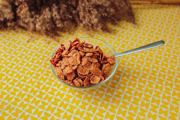 Dunkles getreide mit löffel in der glasplatte. gesunde ernährung, gesundes essen auf dem tisch mit getrockneten blumen.