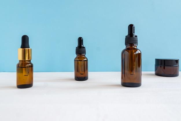 Dunkles glas und transparente kosmetikflaschen mit gesichtsserum oder ätherischem öl auf blauem hintergrund. kosmetikprodukte ohne markenzeichen.