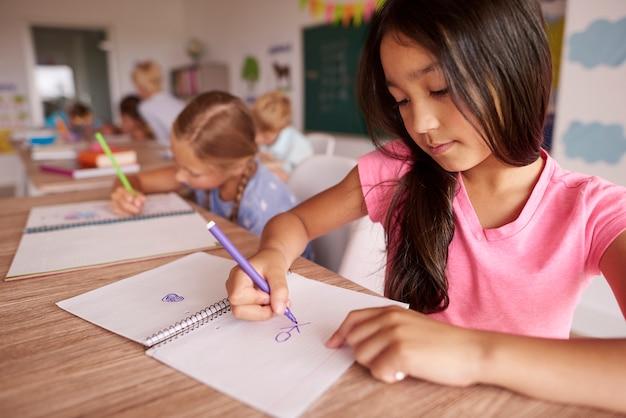Dunkles haarmädchen, das im klassenzimmer zeichnet