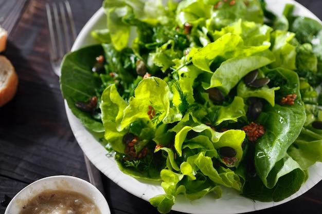 Dunkles hölzernes diätlebensmittel der frischen leinsamen des grünen salats der platte