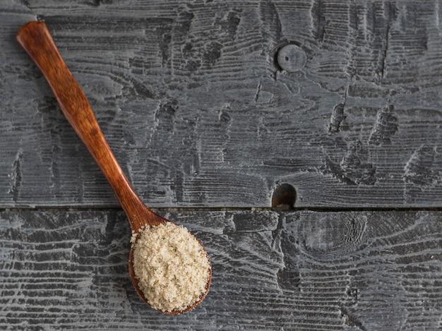 Dunkles holz des löffels mit draufsicht des salzes auf dem tisch. von oben betrachten.