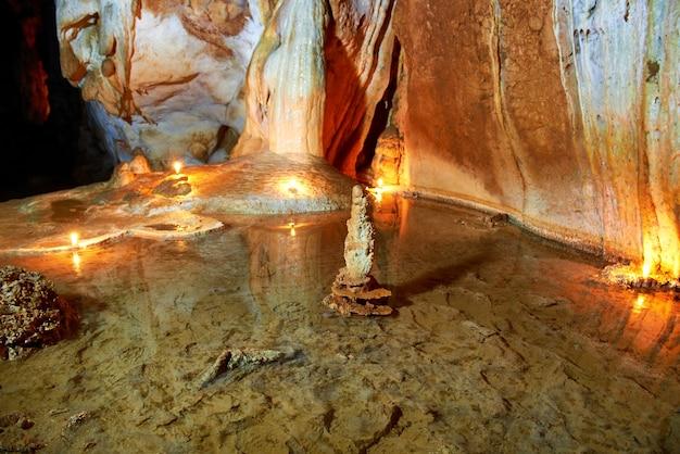 Dunkles inneres der höhle mit unterirdischem see, licht, stalaktiten und stalagmiten