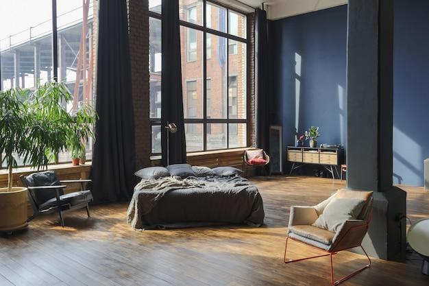 Dunkles interieur eines modernen, stilvollen, riesigen studio-apartments im loft-stil mit säulen und hohen decken.