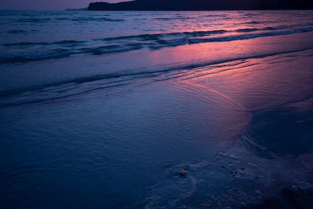 Dunkles meersandstrand und roter sonnenlichtsonnenuntergangdämmerungs-ozeanhintergrund