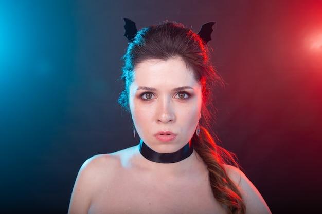 Dunkles mode-, halloween- und menschenkonzept - gotische frau in fledermausohren über dem dunklen hintergrund