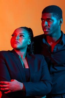 Dunkles neonporträt des jungen afroamerikanermannes und der jungen afroamerikanerfrau. rotes und blaues licht.