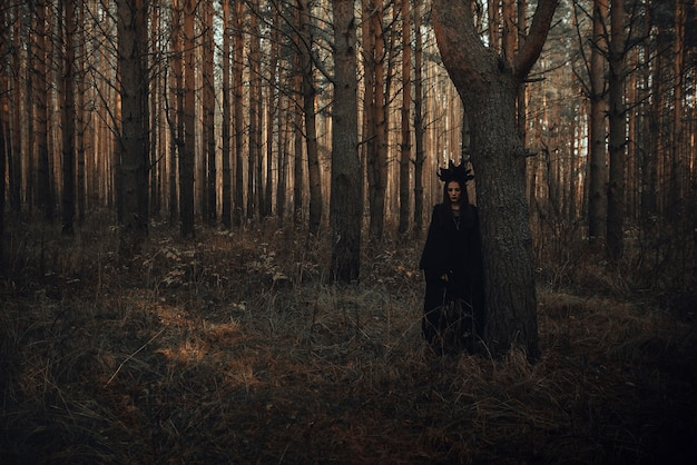 Dunkles porträt einer erschreckenden hexe im schwarzen kostüm im wald