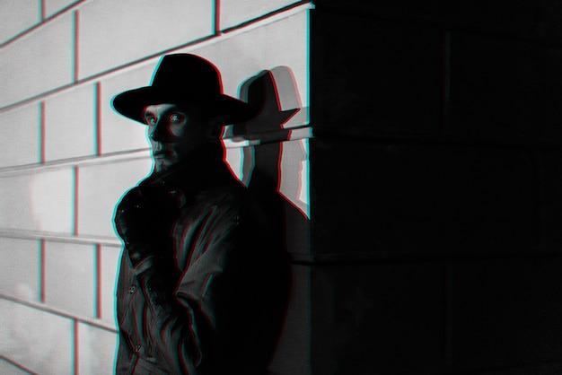 Dunkles porträt eines mannes in einem regenmantel mit einem hut nachts auf der straße. schwarzweiß mit 3d-glitch-virtual-reality-effekt