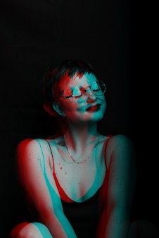 Dunkles porträt eines sexy mädchens, das auf einem stuhl sitzt. rauschen wird dem foto überlagert schwarzweiß mit glitch-effekt