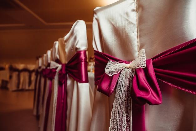 Dunkles rosa- und milchtuch verschönern die bedeckten stühle