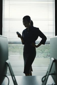 Dunkles schattenbild der frau mit dem smartphone, der im büro am fenster mit vorhängen steht