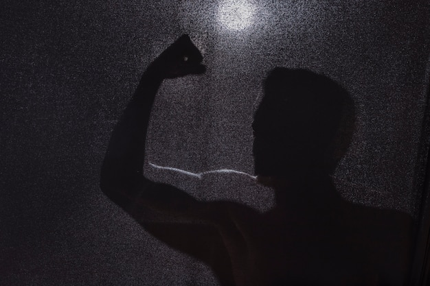 Dunkles schattenbild des kerls bizeps zeigend