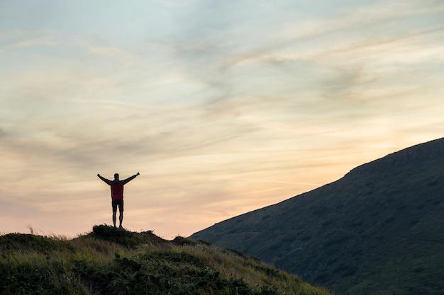 Dunkles schattenbild eines wanderers, der einen berg bei dem sonnenuntergang anhebt seine hände stehen auf gipfel wie ein sieger klettert.