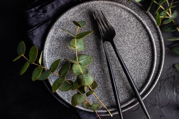 Dunkles steinzeug mit schwarzem besteck auf schwarzem betontisch, dekoriert mit frischen grünen eukalyptusblättern