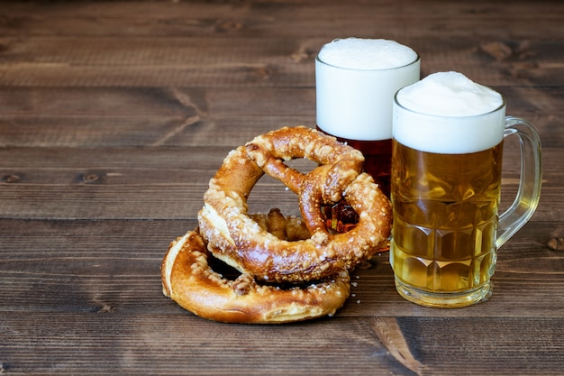 Dunkles und helles bier, brezeln auf dem holz