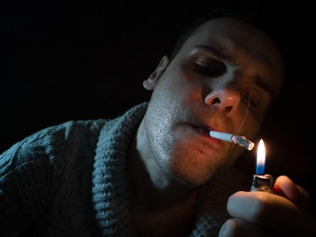 Dunkles und mürrisches bild eines jungen mannes, der raucht
