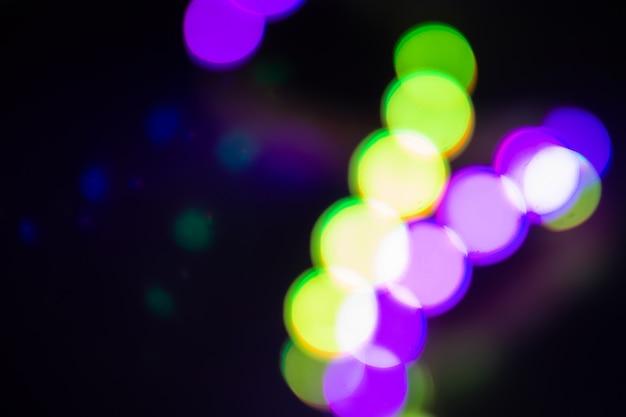 Duotone grüne und violette verschwommene neonlichter auf schwarz. nachtparty-konzept.