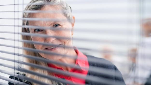 Durch die jalousien. erfolgreiche geschäftsfrau, die durch das bürofenster schaut. geschäftsleute