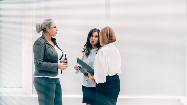 Durch die jalousien redet eine gruppe von geschäftsfrauen in der bürolobby
