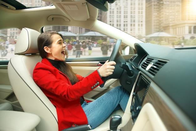 Durch die stadt fahren. junge attraktive frau, die ein auto fährt. junges hübsches kaukasisches modell in der eleganten stilvollen roten jacke, die am modernen fahrzeuginnenraum sitzt. geschäftsfrau konzept.